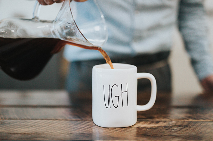 Pouring coffee into a mug that says ugh
